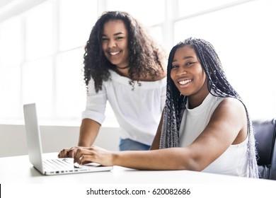 Two Happy teen taking a break at desk in her office