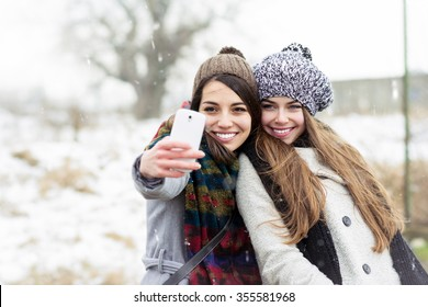Two happy teenage girlfriends taking a selfie on smartphone outdoors in winter. Young women in winter outfits and knitted beanie hats, photographing themselves using cellphone camera. No retouch.