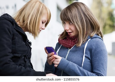Two happy teenage girls looking at smartphone