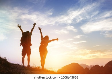 Two happy tourists backpackers greetings sunrise or at mountains top