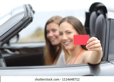 Two happy tourists showing a blank credit card inside a convertible a car