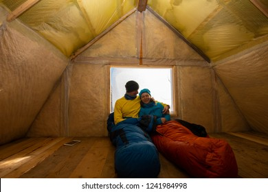 Two happy travelers are resting in the old mountain hut, sitting in a sleeping bags next to a window and having fun. Awesome adventure in winter wilderness.