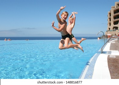 Two happy twin brothers are jumping into infinity swimming pool at the resort with ocean at the background
