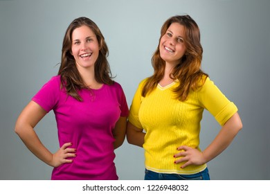 Two Happy Twin Sisters Smiling on Gray Background