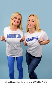 two happy volunteer girls on blue background