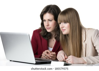 Two happy women blonde and brunette, sitting together in front of a laptop