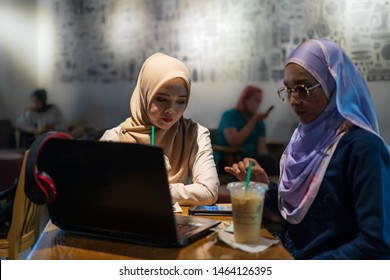 Two happy women with coffee doing job and discussing with laptop in coffeeshop, indoor, selective focus.