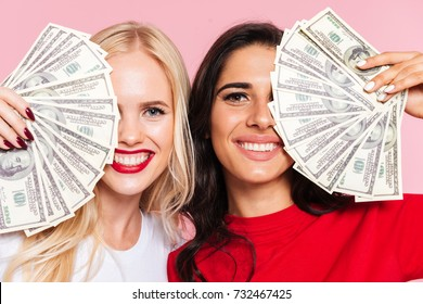 Two happy women covering their half faces and looking at the camera over pink background