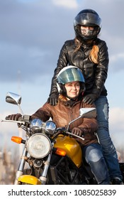 Two happy women driving together on one bike, passenger standing behind driver seat