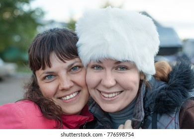 Two happy women embracing together, leaning cheek to cheek and smiling, facial portrait