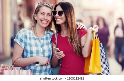 Two happy women enjoying in shopping, having fun together in the city. Consumerism, fashion, lifestyle concept