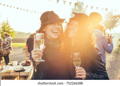 Two happy women outdoors drinking white wine having fun in countryside