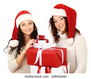 Two happy women in santa hats with gift boxes standing on white background isolated