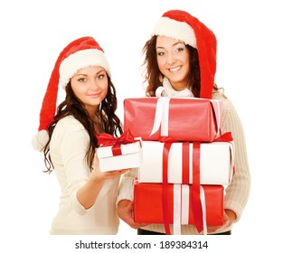 Two happy women in santa hats with gift boxes standing on white background isolated.