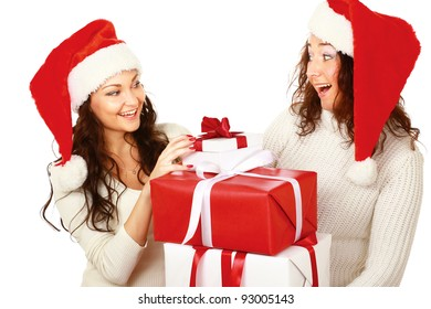 Two happy women in santa hats with pile of gift boxes standing on white background isolated.
