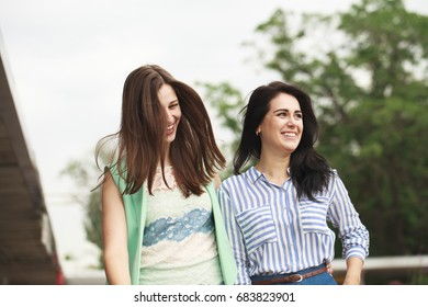 Two happy women walking in the summer park