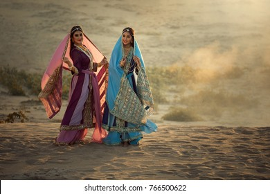 Two happy women wearing Iran or Arabian traditional dress stand by the sand.