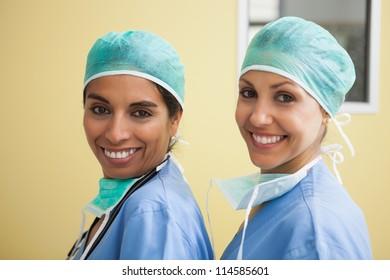 Two happy women wearing scrubs in hospital room against yellow wall