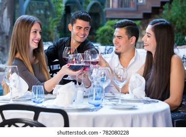 Two happy young adult couples on double date in garden of restaurant sitting at round table outdoors holding glasses of red wine and cheering.