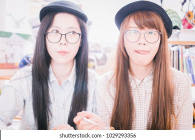 Two Happy Young Asian Girls with glasses and funny faces eating cake in cafe, having fun and licking food dessert stain on lip Concept of Best Friends hang out having good time together in coffee shop