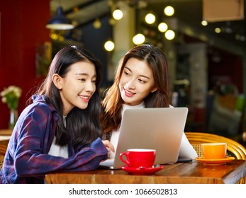 two happy young asian women sitting in coffee shop looking at laptop computer together.