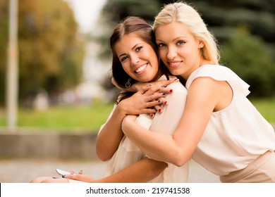 Two happy young attractive women friends for a walk. One hugs another