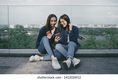 Two happy young best friends using social media on their smartphone