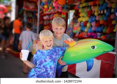 Two happy young boy children are smiling with their slushie and toy prize a a small town American carnival.