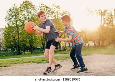 Two happy young boys playing basketball outdoors on a sports field in spring backlit by the warm glow of the evening sun