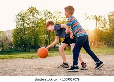 Two happy young boys playing basketball outdoors on a sports field in spring backlit