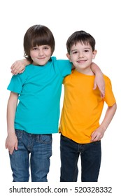 Two happy young boys are standing against the white background