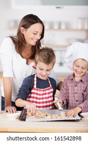 Two happy young brothers, one in a chefs toque and one in a colorful red and white apron, baking cookies in the kitchen watched over by their attractive mother