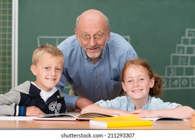 Two happy young children with their elderly male teacher in the classroom posing together in front of the blackboard smiling at the camera