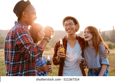 Two happy young couples talking and drinking beer and soda together