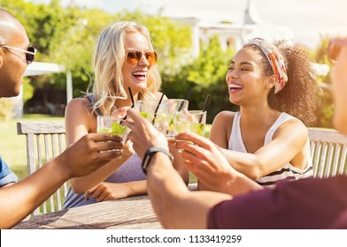 Two happy young couples toasting with glasses of cocktails. Young beautiful women and men drinking lemonade and smiling. Cheerful guys and multiethnic girls friends raising a mojito toast at party.