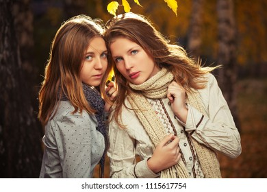 Two happy young fashion girls walking in autumn park Stylish teenage models wearing white shirt and scarf outdoor