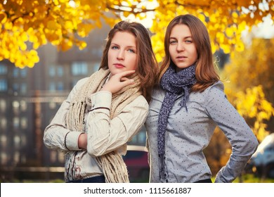 Two happy young fashion girls walking in city street Stylish teenage models wearing white shirt and scarf outdoor