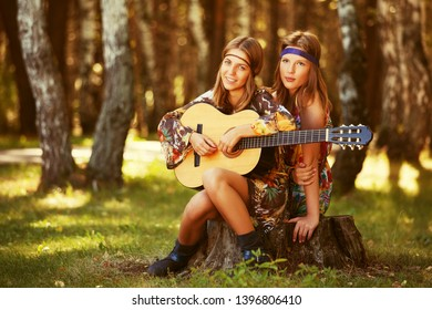 Two happy young fashion girls with guitar in summer forest Stylish teenage model in floral dress
