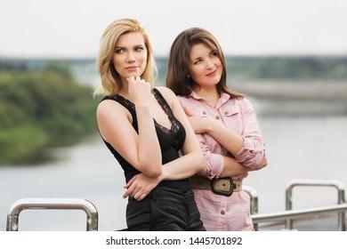 Two happy young fashion women walking outdoor