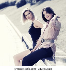 Two happy young fashion women sitting on the bench in a city park
