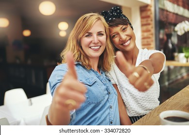 Two happy young female friends giving a thumbs up gesture of approval and success as they sit arm in arm in a cafeteria enjoying coffee together