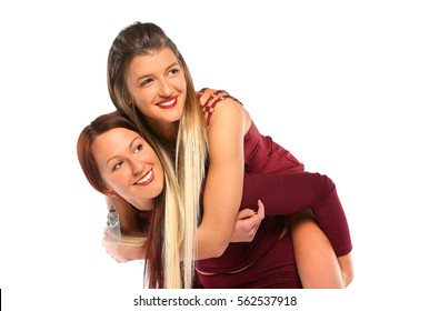 Two happy young girls with beautiful smile love piggy back in studio