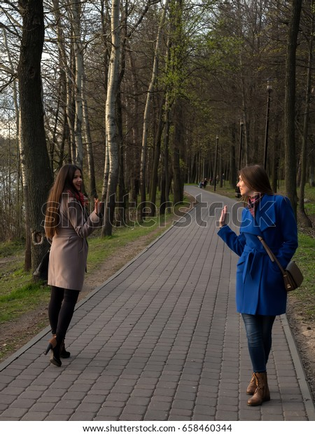Two happy young girls met each other in the park. Female friendship. Walk in the park outdoors.