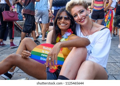 Two happy young girls smiling and celebrating Milano Pride 2018, manifestation of gay, lesbians, asexuals, bisexuals, intersexual and queer pride. Milan, Italy. June 30, 2018.