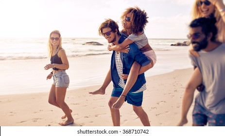 Two happy young men giving their girlfriends piggyback rides at the beach. Group of friends enjoying beach holidays.