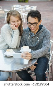 Two happy young people looking into mobile device while sitting at a table in outdoor cafe, closeup