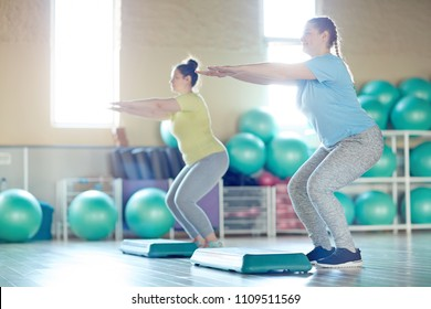 Two happy young plus-sized women exercising with step platforms in fitness center