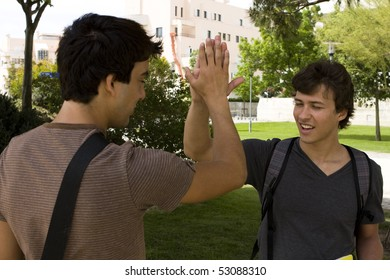 Two happy young student giving a handshake (selective focus)