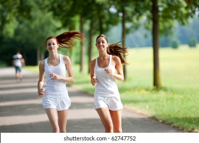 two happy young woman running in a park in a sunny day.