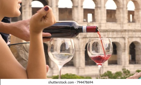 Two happy young woman tourists sitting at the table of a bar restaurant in front of the Colosseum in Rome drink and toast with a glass of italian red wine.